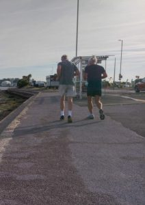 Two joggers running on pavement